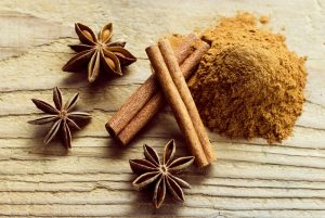 Cinnamon sticks and anise stars over wooden table, above view